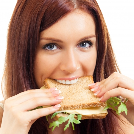 adult sandwich: Portrait of cheerful young woman eating sandwich with cheese, isolated over white background