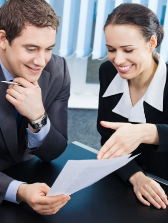 costumer: Two happy smiling cheerful young businesspeople working with documents at office