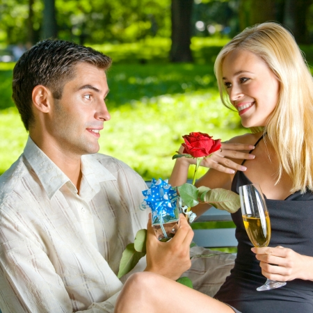 adult valentine: Young happy smiling cheerful couple with gifts, rosa and champagne, outdoor