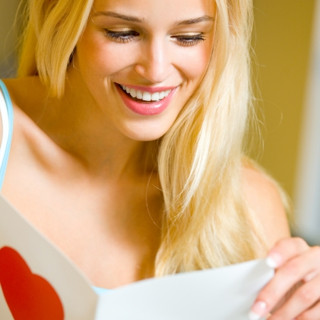 Young happy smiling cheerful beautiful blond woman, reading valentine card, at home photo