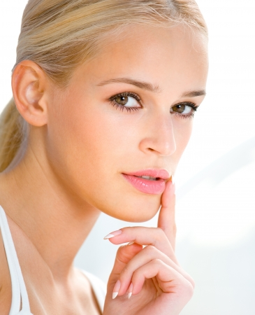 shushing: Portrait of beautiful blond woman with finger on lips Stock Photo