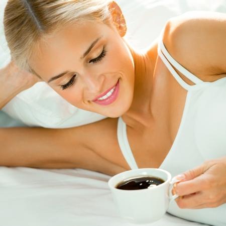 mujer tomando cafe: Feliz sonriente mujer rubia hermosa despertarse con la taza de café en la habitación Foto de archivo