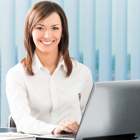 social worker: Portrait of successful happy smiling business woman working with laptop at office Stock Photo