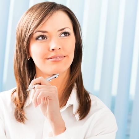 dream planning: Portrait of happy smiling thinking business woman at office