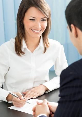 dos personas hablando: Dos alegre sonriente jóvenes empresarios, o mujer de negocios y clientes, trabajando en la oficina