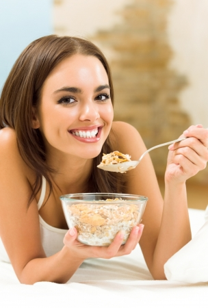 muslin: Young woman eating cereal muslin (flakes)