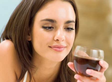 Portrait of young happy smiling cheerful beautiful woman with glass of red wine Stock Photo - 16317384