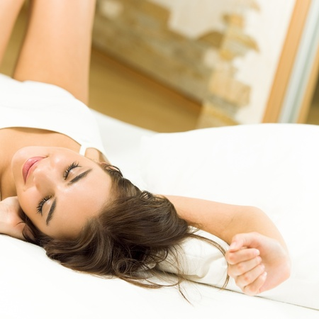 Young beautiful woman sleeping on bed photo