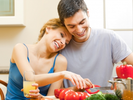 Cheerful young cooking couple prepairing vegetarian salad at home photo