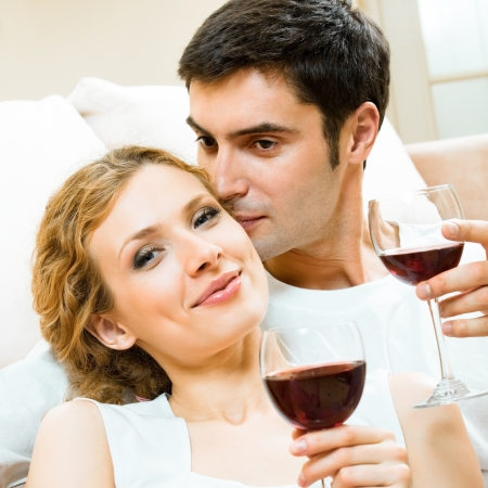 twenty two: Portrait of cheerful smiling couple with glasses of red wine, indoors