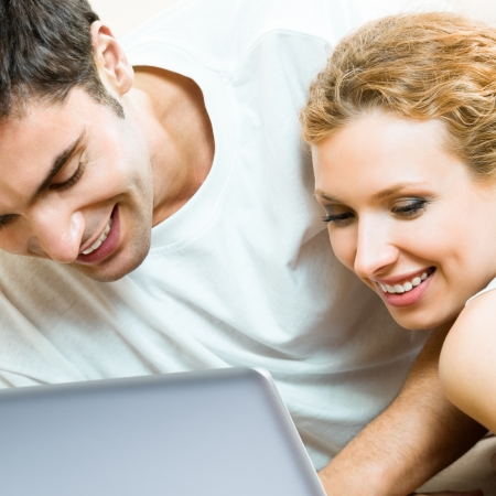 Cheerful couple working with laptop together, at home photo