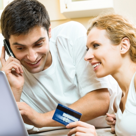 pay bill: Cheerful smiling couple paying by plastic card with laptop, indoors Stock Photo
