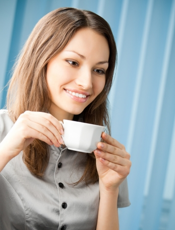 Cheerful smiling business woman drinking coffee at office photo