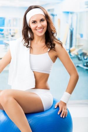 rozradostněný: Mladá veselá žena s úsměvem cvičení s fitball na fitness klubu nebo tělocvičně Reklamní fotografie