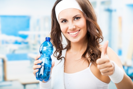 fitness club: Portrait of cheerful young attractive woman showing thumbs up gesture, with bottle of water, at fitness club or gym