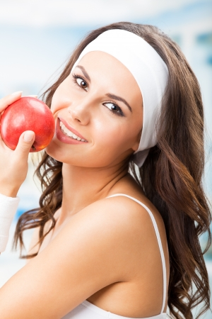 Cheerful young beautiful woman with red apple, at fitness center or gym photo