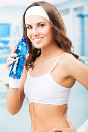 water aerobics: Portrait of cheerful young attractive woman drinking water, at fitness club or gym