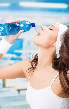Portrait of cheerful young attractive woman drinking water, at fitness club or gym photo