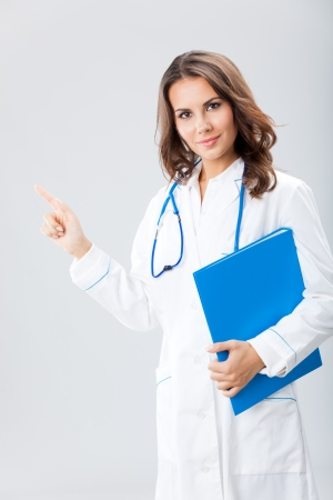 Portrait of young female doctor showing something or copyspase for product or sign text, with blue foder, over grey background Stock Photo - 16499394