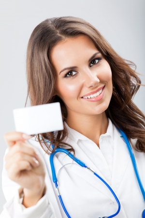 Portrait of happy smiling young female doctor showing blank business card or invitation, over grey background photo