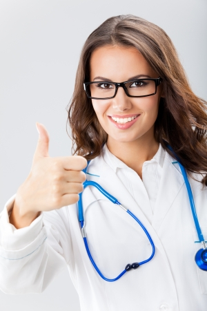 Happy smiling cheerful female doctor with thumbs up gesture, over grey background Stock Photo - 16499407