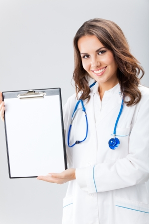 Happy smiling young female doctor showing okay gesture, over grey background Stock Photo - 16499396