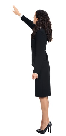 Full body of young business woman pointing at something in her back, isolated over white background photo