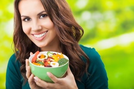 Portrait of happy smiling young woman with vegetarian vegetable salad, outdoors photo