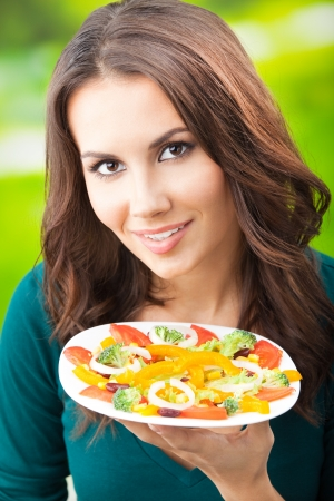 Portrait of happy smiling young woman with vegetarian vegetable salad, outdoors Stock Photo - 16619548