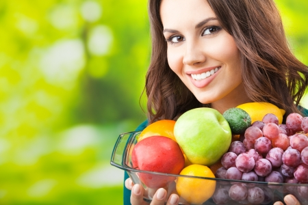 vegetarians: Young happy smiling woman with plate of fruits, outdoors, with copyspace for text or slogan. Stock Photo