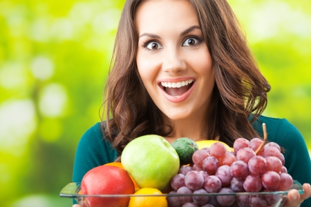 Young happy smiling woman with plate of fruits, outdoors, with copyspace for text or slogan. Stock Photo - 16619544
