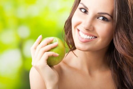 mujeres jovenes desnudas: Joven mujer feliz sonriendo con manzana, al aire libre, con copyspace para el texto o eslogan Foto de archivo