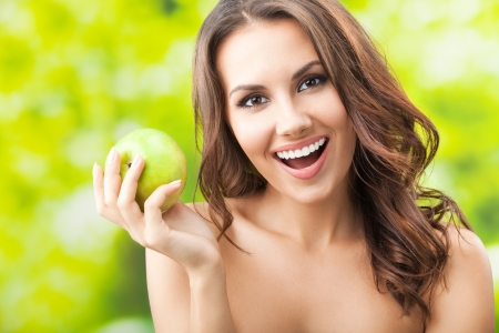 Portrait of young beautiful happy smiling woman with green apple, outdoors Stock Photo - 16674381