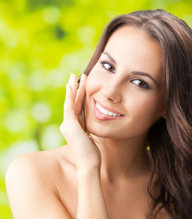 naked young woman: Portrait of happy smiling beautiful young woman touching skin or applying cream, outdoors
