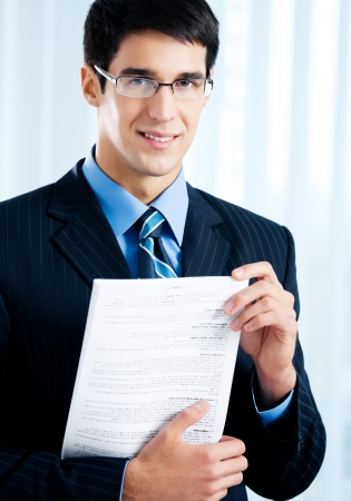 Happy smiling businessman showing document or contract, at office photo
