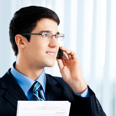 Happy smiling businessman with documents or contract and cell phone, at office photo