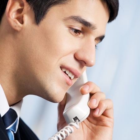 Portrait of young smiling businessman or call center worker with phone at office photo