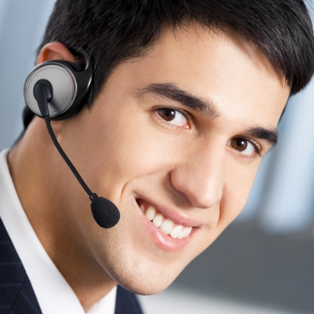 call center agent: Support phone operator in headset at workplace Stock Photo
