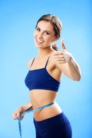 lose up: Cheerful woman in fitness wear with tape, showing thumbs up gesture, over blue background