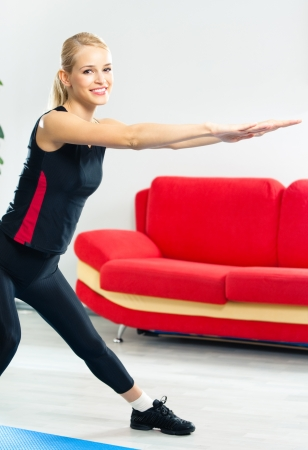 sports wear: Young woman in sports wear doing fitness exercise, indoors