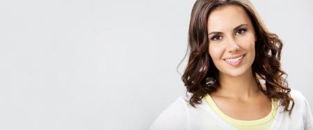eslogan: Retrato de feliz sonriente mujer joven y hermosa, con copyspace para el eslogan anunciar, signo o texto, sobre fondo gris