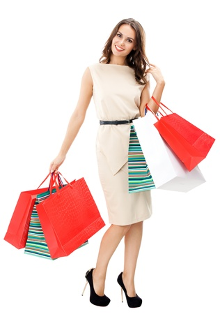 Full body portrait of young happy smiling woman with shopping bags, isolated over white background photo