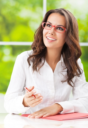 writing on glass: Portrait of young happy smiling business woman in glasses working with documents at office Stock Photo