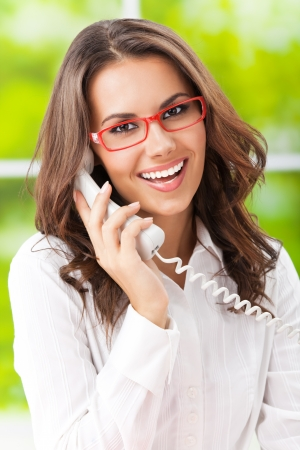 Portrait of happy smiling cheerful beautiful young business woman or support phone worker, at office Stock Photo - 17286507