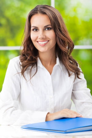 Portrait of young happy smiling business woman working with documents at office photo