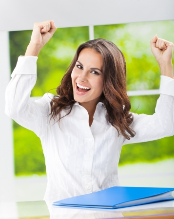 Portrait of happy gesturing smiling young business woman with documents at office photo