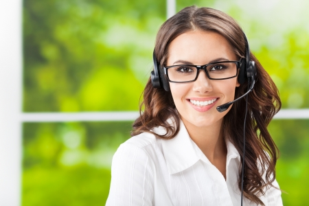 call center office: Portrait of happy smiling cheerful beautiful young support phone operator in headset, at office, with copyspace Stock Photo