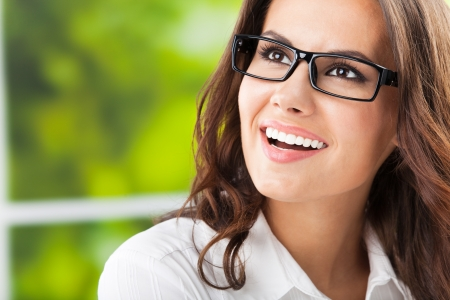 Portrait of young happy smiling cheerful business woman at office, with copyspace Stock Photo - 17286426