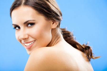 20s naked: Portrait of beautiful young happy smiling woman, over blue background Stock Photo