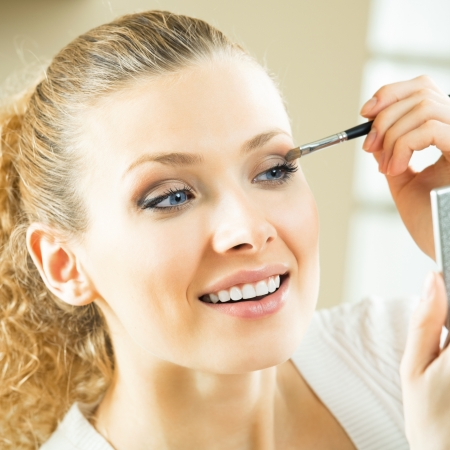 Cheerful smiling woman with mirror and makeup brush Stock Photo - 17383281